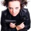 Woman in leather wear holding gun - Stock Photo