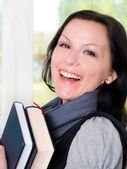 Smiling student woman holding books — Stockfoto
