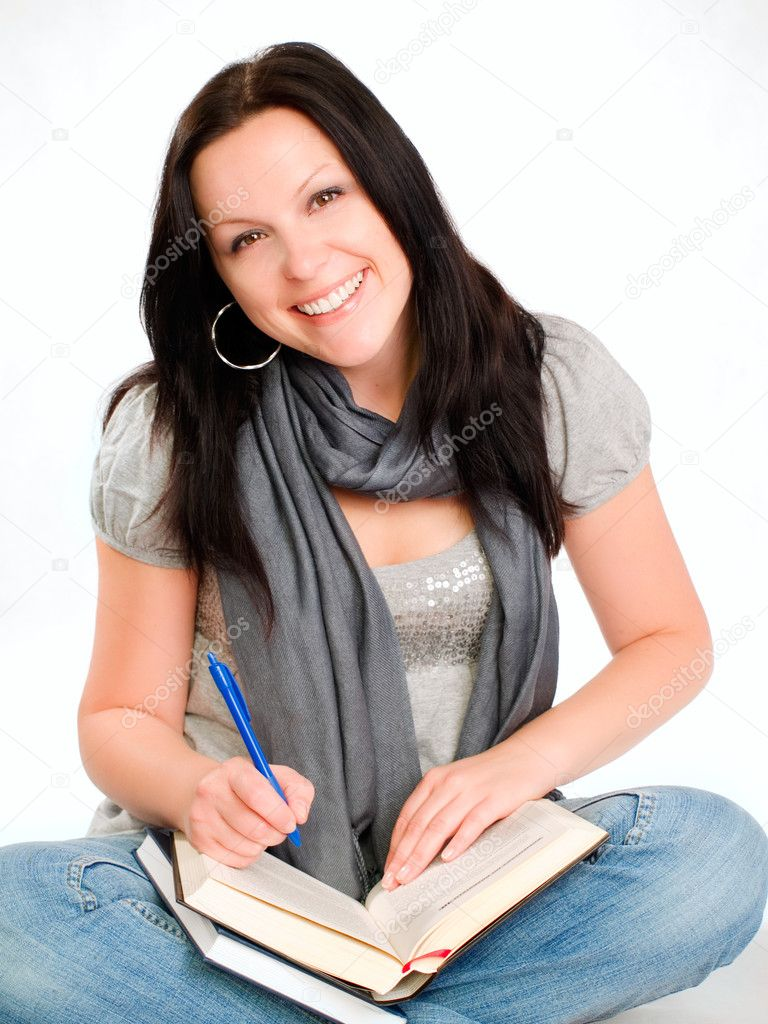 Smiling student woman sitting and making notes in book — Stock Photo #2095073