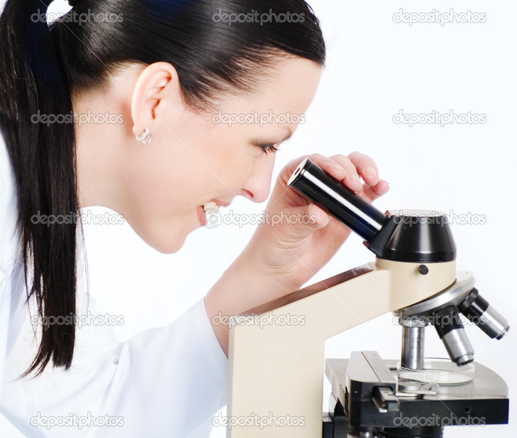 Smiling brunette medical woman researching on a microscope — Stock Photo #2095533