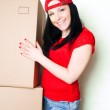 Pretty woman picking up boxes — Stock Photo #2404402
