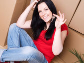 Woman with package holding keys — Stock Photo