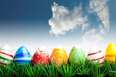 Easter eggs in green grass over blue sky with cl — Stock Photo