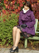 Woman has a rest in park on a bench — Stock Photo