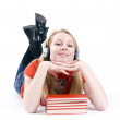 Stock Photo: Girl in headphones with stack of books