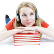 Girl in headphones with stack of books — Stock Photo