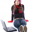 Girl in winter clothes working on laptop - Stock Photo