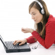 Girl working on laptop and listening mp3 — Stock Photo