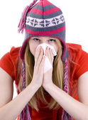 Young woman sneezing in the handkerchief — Stock Photo