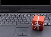 Pequeña caja de regalo en el teclado del ordenador portátil — Foto de Stock