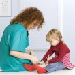 Little girl at female doctor - Stock Photo