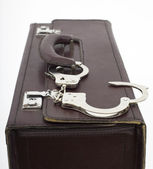 Suitcase from pinned open handcuffs — Stock Photo