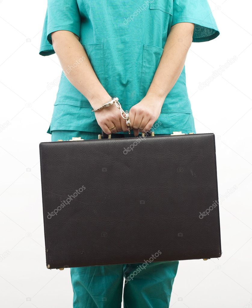 Human body in green medical clothes from pinned to suitcase with handcuffs hand  — Stock Photo #1811783