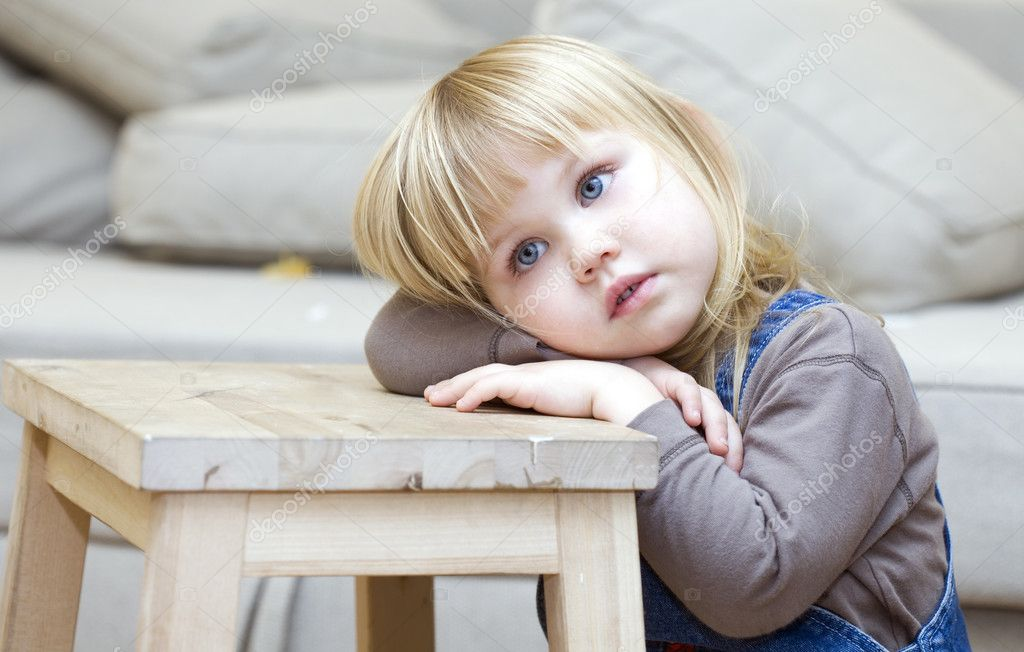 Sad, frighten or thoughtful little girl with blond hair. Sitting on floor, lying on leaning on wooden stool hands face  — Photo #1812927