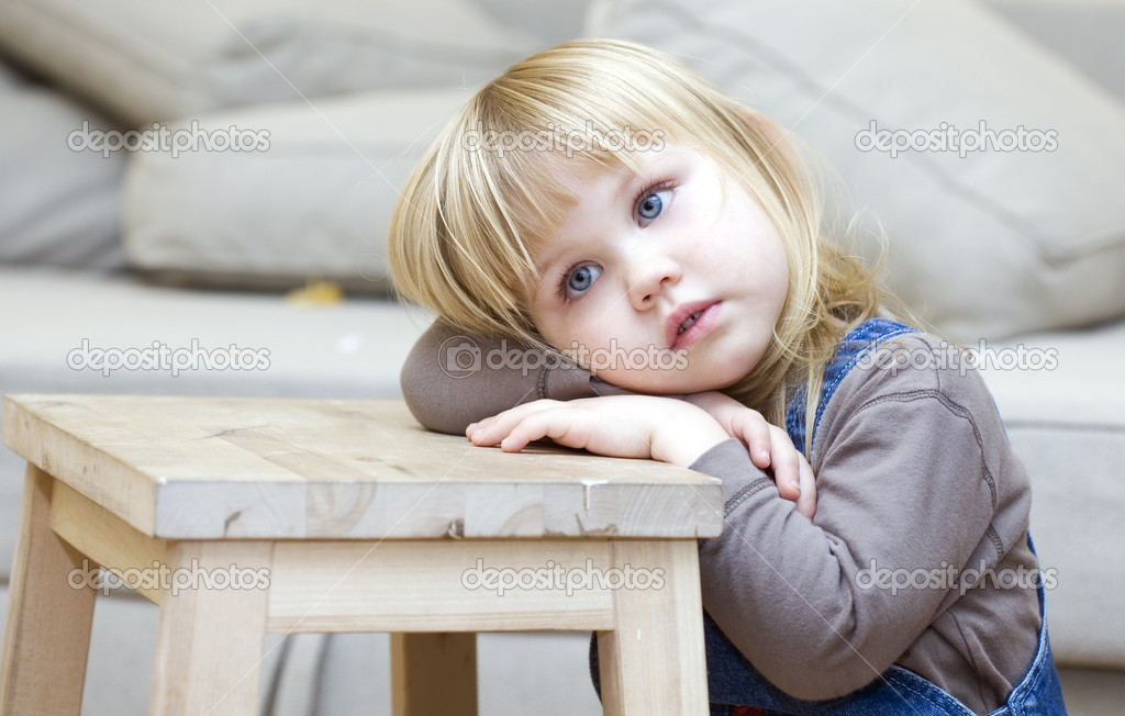 Sad, frighten or thoughtful little girl with blond hair. Sitting on floor, lying on leaning on wooden stool hands face  — Stock Photo #1812927