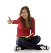 Young woman keeping book and thumb up — Stok fotoğraf