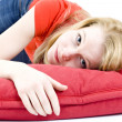 Young woman lying on the red pillow — Stock Photo