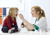 Little girl at lady doctor drinks syrup — Stock Photo