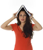 Young woman keeping book on her head — Stock Photo
