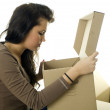 Stock Photo: Girl with curiosity looks to carton box