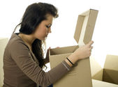 Girl with curiosity looks to carton box — Stock Photo