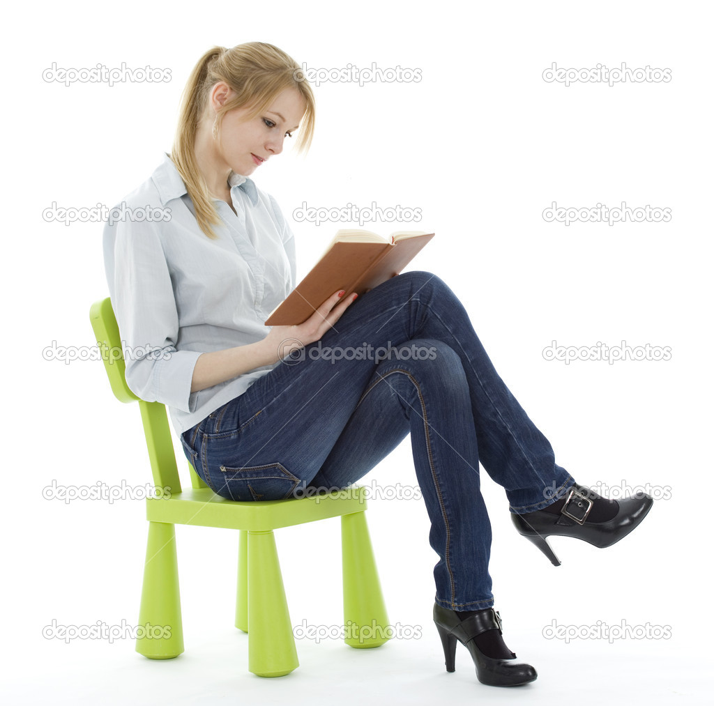 Sitting on the green, child's chair young woman reading book — Stock Photo #2373777
