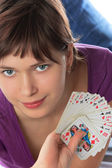 Young girl holds a pack of playing cards — Stock Photo