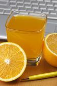 Oranges, juice and laptop. — Stock Photo