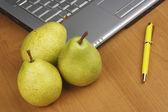 Peras e laptop na mesa de madeira — Foto Stock