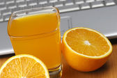 Oranges, juice and laptop. — Stockfoto