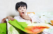 Yawning lady on the bed covered by colorful blanket — Stock Photo