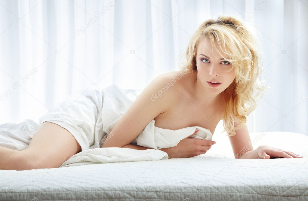 Sexy lady laying on the bed and covered by the blanket — Stock Photo #1627147