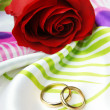 Foto Stock: Red rose and golden rings