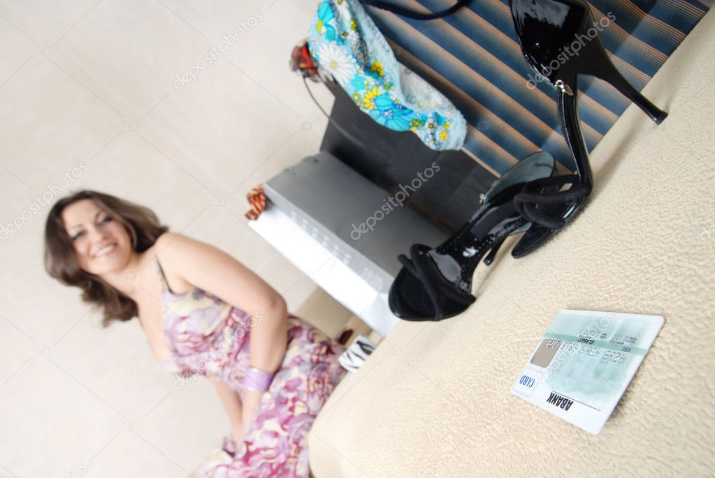 Credit card on a sofa and smiling woman with purchase on a background — Stock Photo #1772426