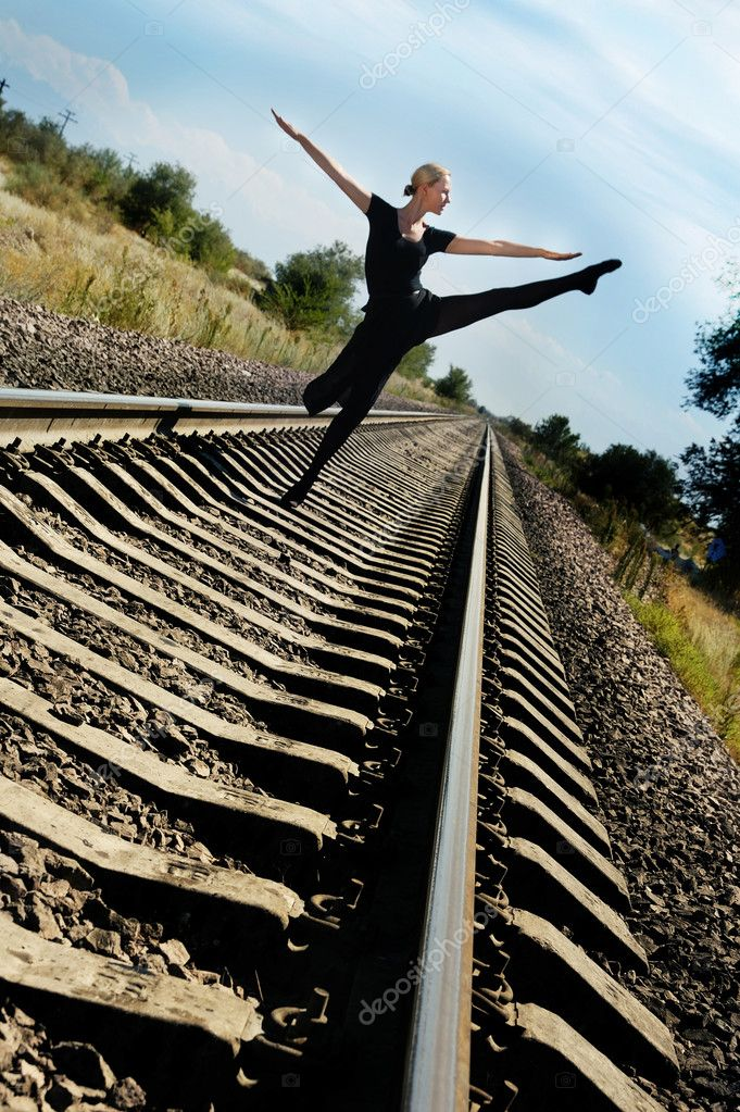 Woman dances on railway and does not fear the train — Stock Photo #1772520