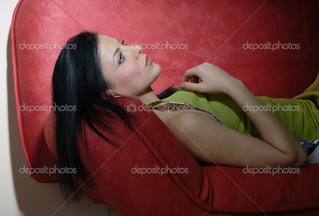 Portrait of the resting lady laying on the red sofa — Stock Photo #1773496