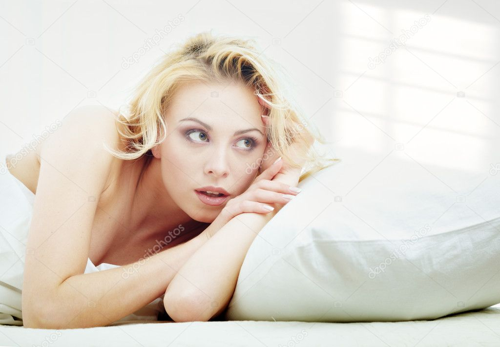 Young blond lady laying in a bedroom with shadows on the wall from the window — Stock Photo #1774165