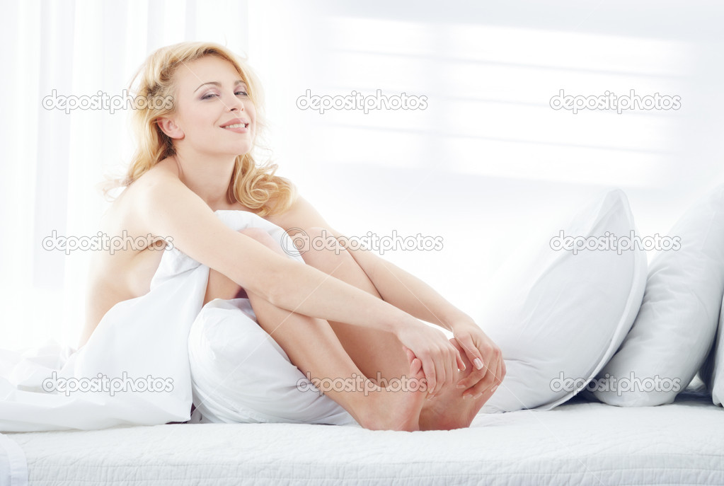Young blond lady sitting in a bedroom and massaging her foot. Window shadows on the wall — Stock Photo #1774193