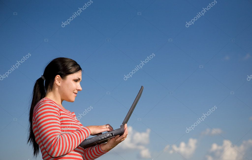 Attractive brunette woman with laptop on sky background — Stock Photo #1640545