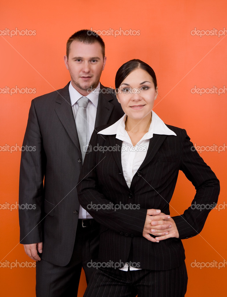 Woman and man in team standing on orange background — Stock Photo #1642464