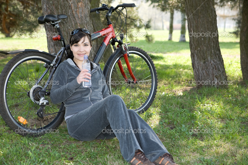 Happy woman with bike in park — Stock Photo #1645438
