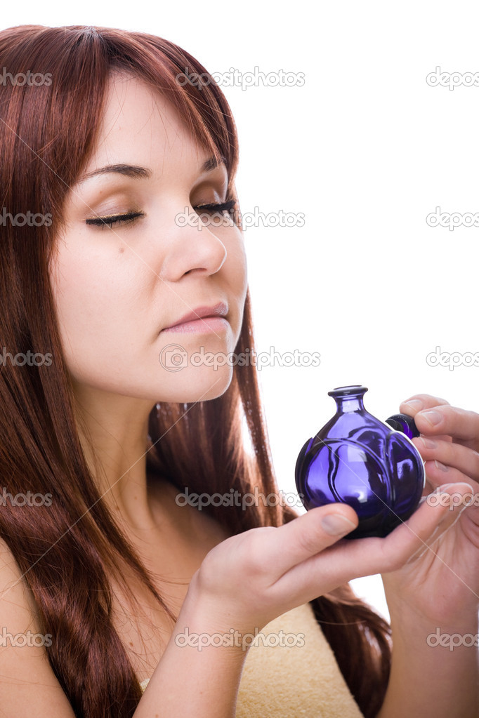 Attractive young woman with perfume bottle. over white background — Stock Photo #1679858