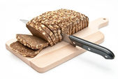 Sliced wholemeal bread on kitchen board — Stock Photo