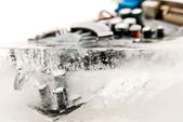 Frozen computer part in ice cube — Stock Photo