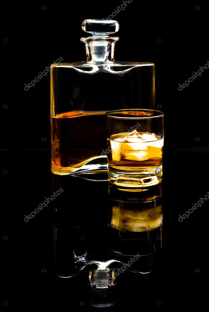 Carafe of scotch whiskey or bourbon and drink with ice on black background — Stock Photo #1645256