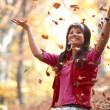 Beautiful girl with falling leaves — Stok fotoğraf