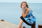 Beautiful woman sitting on the mooring — Stock Photo