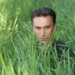 Man's portrait in the grass — Stock Photo