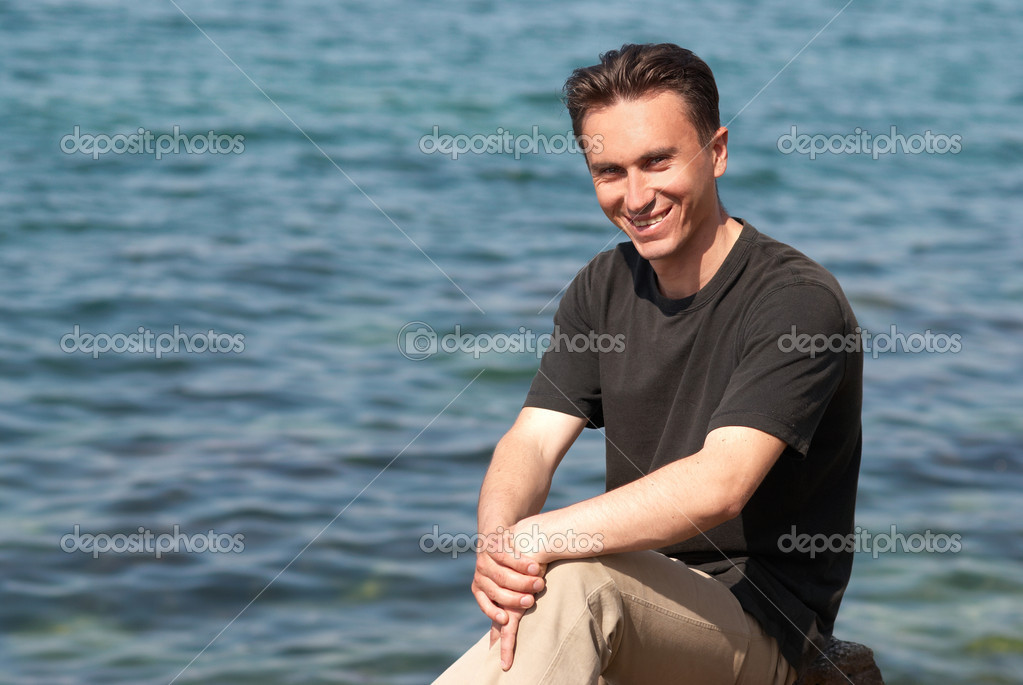 Portrait of young man sitting near the blue sea — Stock Photo #2279399