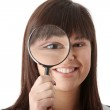 Woman looking into a magniying glass — Stock Photo
